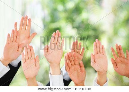 As pessoas levantam as mãos acima sobre fundo verde