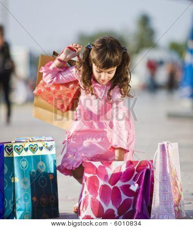 Cute Girl Picking Up Shopping Bags