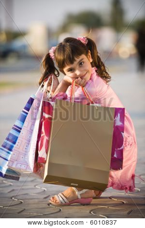 Cute Girl Squatting In The Street With Shopping Bags