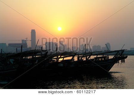 Bahrain city silhouette and fishing dhow in sunset