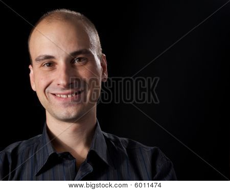 Face Of A Smiling Man. Black Background