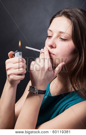 Beautiful Young Woman Is Smoking Cigarette On Black Background