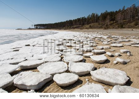 Round Ice Floes On The Sandy Shore.
