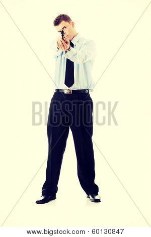 Gun control concept - businessman with handgun, isolated on white