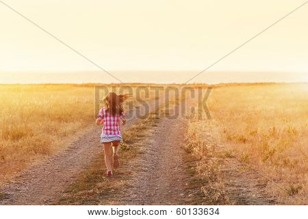 Little girl running in backlit meadow