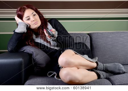 Bored young woman of sofa with tv remote