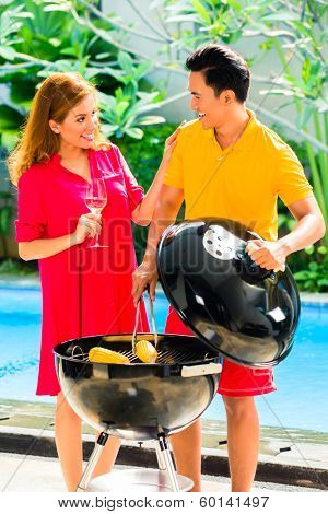Asian handsome couple drinking wine and having barbecue party or BBQ outside at the pool with grilled corn cobs