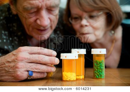 Man And Woman Looking At Prescription Medications