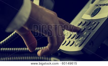 Man Dialing Out On A Landline Telephone