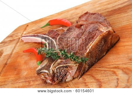 savory : roasted beef spare rib on wooden plate with cutlery and thyme isolated over white background