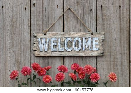 Wood welcome sign with flower border by wooden fence