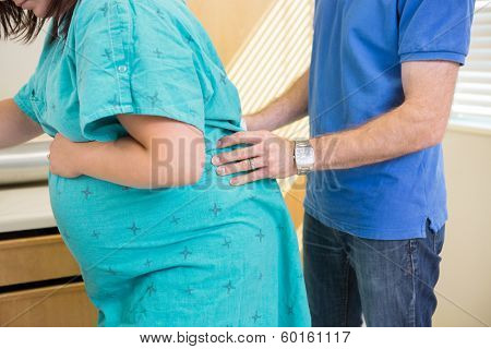 Husband providing acupressure pain relief to wife undergoing a contraction