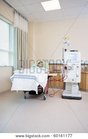 Young male patient sleeping while receiving renal dialysis in hospital room