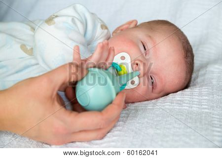 Mother using bulb syringe to clean unhappy infant baby's nose