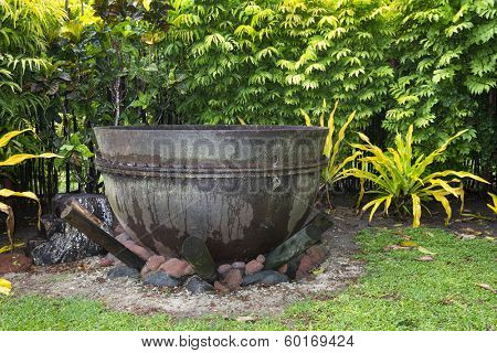 An ancient cast iron cauldron rests on a fire pit ready to burn.