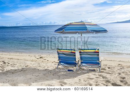 Two blue beach chairs with umbrella on the water's edge of a tropical beach
