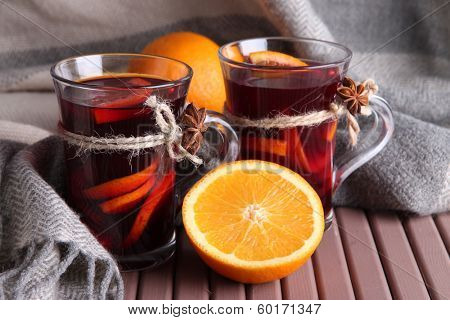 Mulled wine with oranges on table on fabric background