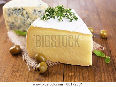 Tasty Camembert cheese with thyme and olives, on wooden table