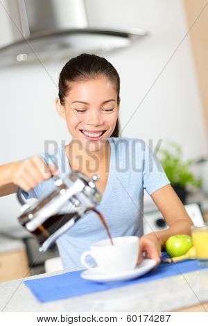 Woman eating breakfast and drinking coffee in the morning. Girl pouring coffee from french press at home in kitchen. Beautiful mixed race Asian Caucasian female model smiling happy.