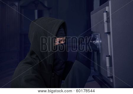 A Robber Trying To Open A Safety Box