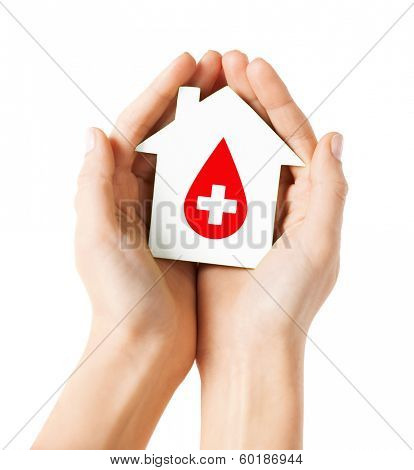 healthcare, medicine and blood donation concept - hands holding hands holding white paper house with red donor sign