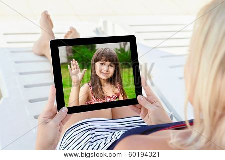 Woman In A Bathing Suit Lying On A Chaise Lounge With A Tablet And Communicates By Video Voice Chat