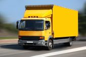 stock photo of delivery-truck  - A yellow truck traveling on a road - JPG