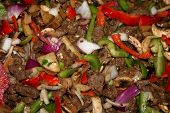 stock photo of deer meat  - Beef and deer meat cooking for fajitas - JPG