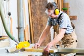 stock photo of hand cut  - Carpenter working on an electric buzz saw cutting some boards - JPG