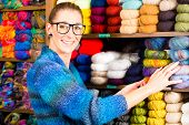 stock photo of knitwear  - Young woman buying colorful wool and yarn for their hobby in a knitting shop - JPG