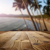 stock photo of combustion  - wooden table on the beach with palms - JPG