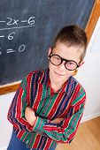 foto of eminent  - Eminent schoolboy wearing glasses standing in front of chalkboard - JPG