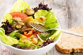 picture of sauteed  - Sauteed brussels sprouts in a mixed leafy green salad with tomato being eaten with a slice of fresh brown bread for an enjoyable light healthy lunchtime meal - JPG