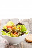 picture of sauteed  - Healthy vegetarian salad with sauteed brussels sprouts in a mixed leafy green salad with tomato and radish served on an old grunge rustic wooden table vertical orientation over white with copyspace - JPG