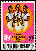 GUINEA - CIRCA 1975: A stamp printed in Guinea shows an african women playing guitars, circa 1975.