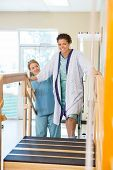 stock photo of upstairs  - Portrait of female patient being assisted by nurse in moving upstairs - JPG