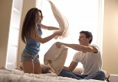 image of pillow-fight  - Portrait of happy loving couple having a pillow fight in bed - JPG
