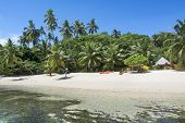 image of cabana  - A look at a Fijian tropical resort from the water showing its lush surroundings and recreational kayaks on the beach along with a small - JPG