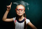 foto of clever  - Genius girl in red glasses near blackboard in master hat - JPG