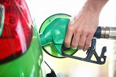 Gas station pump. Man filling gasoline fuel in green car holding nozzle. Close up.