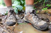 foto of wet feet  - Hiking shoes on hiker in water puddle in rainforest - JPG