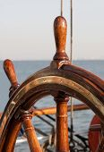 stock photo of ship steering wheel  - Classic wood steering wheel against the sea - JPG