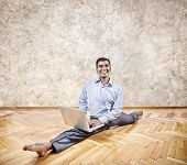 stock photo of do splits  - Happy Indian businessman doing yoga with laptop in the office - JPG