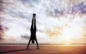 pic of yoga silhouette  - Handstand yoga pose by man silhouette on the beach near the ocean in India - JPG