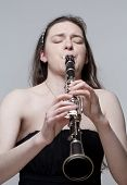 foto of clarinet  - Portrait of Young Female Musician Playing Clarinet - JPG