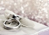 stock photo of bowing  - Pair of wedding rings on top of silver gift box with bow - JPG