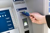 foto of plastic money  - Businessman puts credit card into ATM to withdraw money - JPG