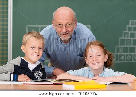 Two Happy Young Children With Their Teacher