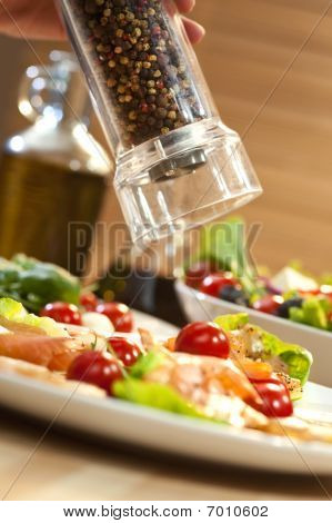 Grinding Pepper Onto Seafood Salad With Smoked Salmon And Shrimp