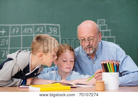 Young Boy And Girl In Class With A Teacher